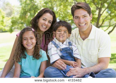 Familien lächelnd outdoors sitzend