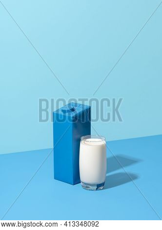 Milk Box And A Glass Of Milk On A Blue-colored Table. Blank Carton Box With Milk, Minimalist On A Bl