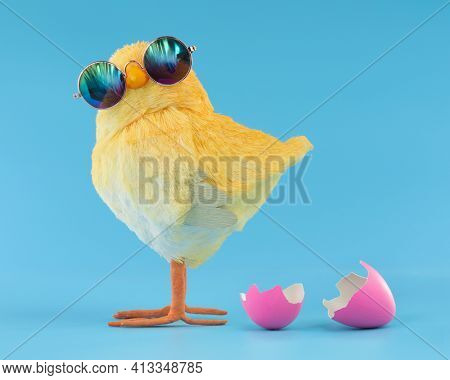 Easter decoration of a yellow chick wearing silly sunglasses with a pink cracked, hatched Easter egg.