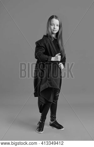 Black And Whit Studio Portrait Of A Young Girl With Brown Hair, With Long Hair, On A Gray Background