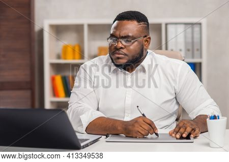Freelance Designer Workplace At Home Office. Young African-american Man Works Using A Computer, Grap
