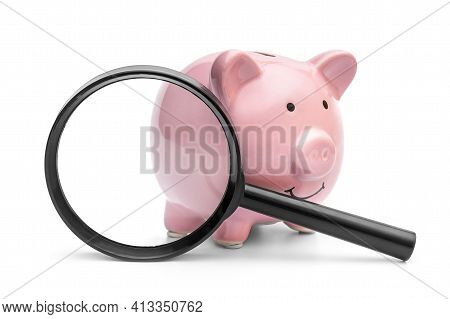 Piggy Bank With Magnifying Glass On White.