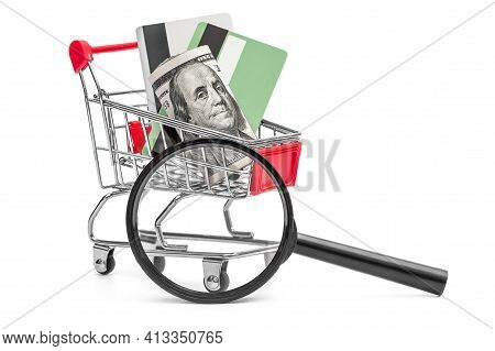 Magnifying Glass And Shopping Cart With Money And Credit Cards On White.