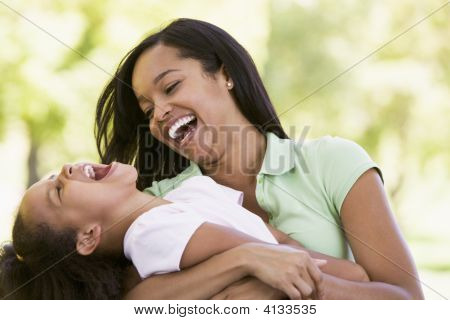 Woman And Young Girl Outdoors Embracing And Laughing
