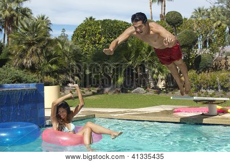 Happy man about to dive in swimming pool with woman floating in inflatable ring