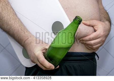 A Fat Man Holds A Scale And A Bottle Of Beer In His Hand With The Other Hand He Holds A Fold Of Fat