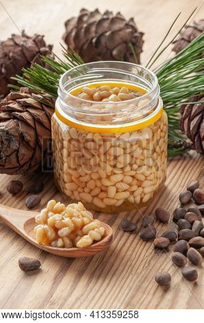 Pine Nut With Honey In A Transparent Jar. The Jar Is Open. Nearby Is A Wooden Spoon With Honey And N