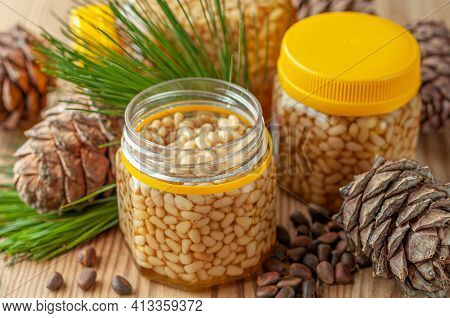 Pine Nut With Honey In A Transparent Jar. The Jar Is Open. Nearby Are Pine Nuts, Cones And Needles.