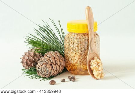 Pine Nut With Honey In A Transparent Jar With A Yellow Lid. Nearby Is A Wooden Spoon With Nuts And H