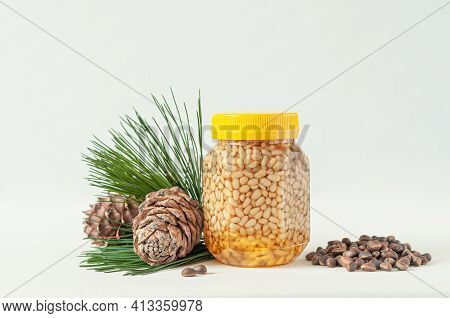 Pine Nut With Honey In A Transparent Jar With A Yellow Lid. Nearby Are Pine Cones, Pine Needles And