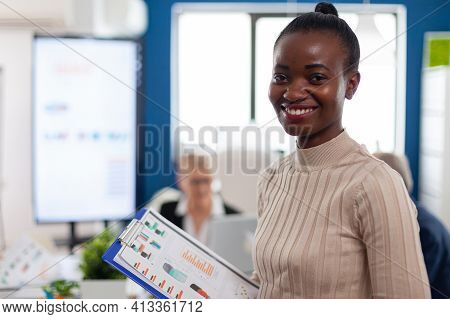 African Woman Manager Looking At Camera Smiling, Holding Clipboard, While Diverse Coworkers Talking