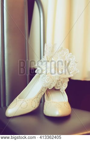 Tinted Photo With White Wedding Shoes And A Garter Belt For The Bride
