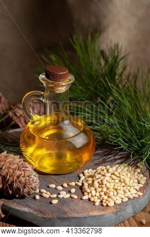 Pine Nut Oil. On A Wooden Background. Nearby Pine Nuts And Cones. View From Above.
