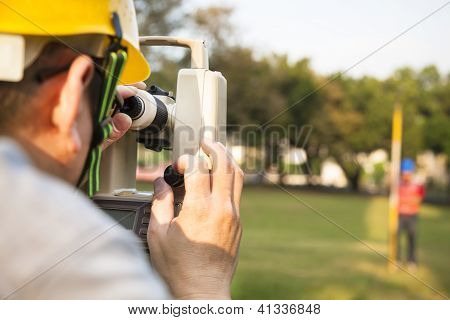 Surveyor engineer with partner making measure on the field poster