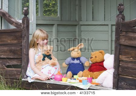 Young Girl In Shed Playing Tea And Smiling