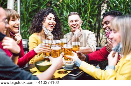 Young People Toasting Beer Wearing Open Face Mask - New Normal Life Style Concept With Friends Havin
