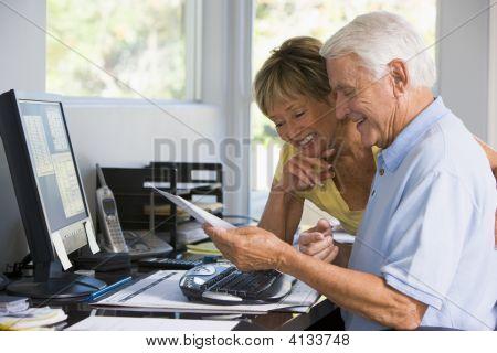 Casais em Home Office, com computador e papelada sorrindo