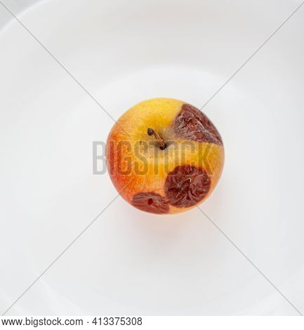 Close-up Of A Rotting Apple Isolated On A White Background With A Copy Space. Biofruits Tend To Rot