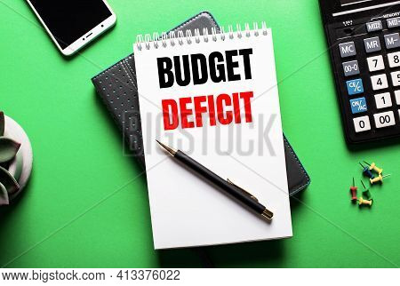 On A Green Background - A Telephone, A Calculator And A Diary With The Inscription Budget Deficit