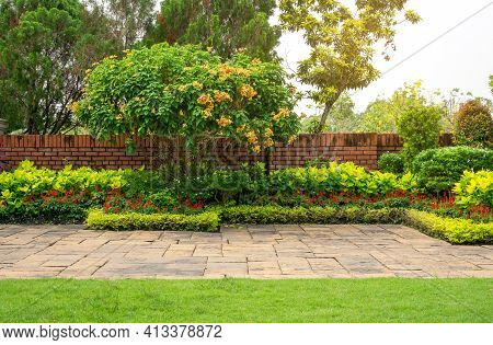 Backyard English Cottage Garden, Colorful Flowering Plant And Green Grass Lawn, Brown Pavement And O