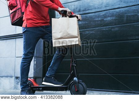 Rider Man Delivering Meal To Customers House With Electric Scooter - Ecological Fast Delivery Food C