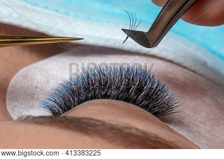Treatment of Eyelash Extension in blue color Lashes. Eyes with Long Eyelashes and face with facemask