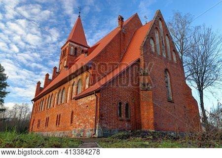 Former Lutheran Kirche, Now Orthodox, With A Red Brick Tower Against The Sky. Kaliningrad Region. Ea