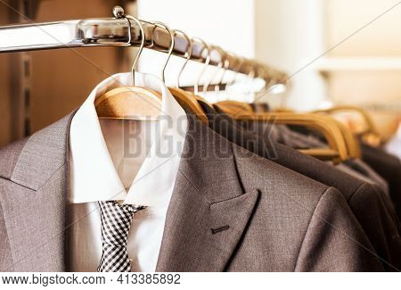Mens Suits And Formal Shirts With Ties On Wooden Hangers In A Clothes Store