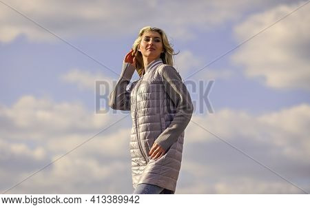 Windy Day. Girl Jacket Cloudy Sky Background. Woman Fashion Model Outdoors. Woman Enjoying Cool Weat