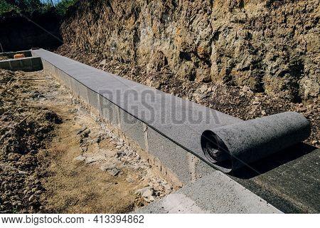 Horizontal Waterproofing. Long Line Of Rolled Bitumen Waterproofing Material In Two Layers Lies On T