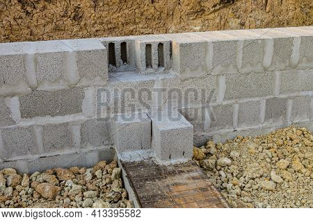 Construction Of Stone Walls Of A Building From Hollow Concrete Blocks On Heavy Granite Gravel. Mason