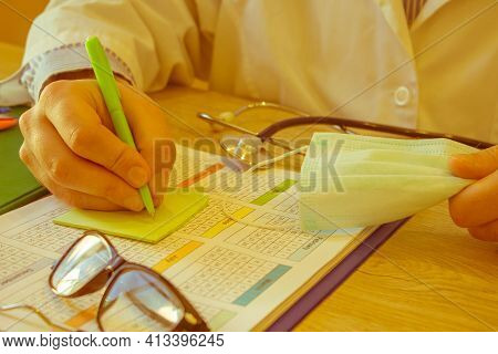Physician Working With Paper In Hospital Office Room. Therapeutist Sitting At Working Table Making S