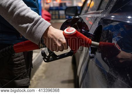 A Refueling Gun In A Man's Hand Is Inserted Into The Gas Tank Of A Car. Evening Time. Refueling, Pet
