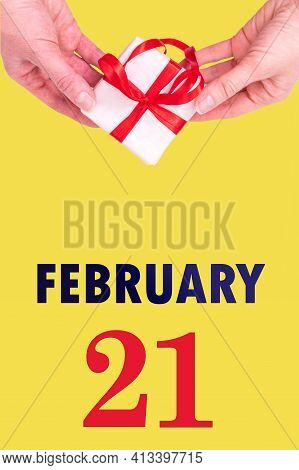 February 21st. Festive Vertical Calendar With Hands Holding White Gift Box With Red Ribbon And Calen
