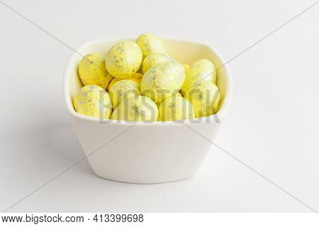Yellow Chocolate Coated Easter Eggs Candies On A Bowl Isolated On A White Table, Tasty Sugary Desser