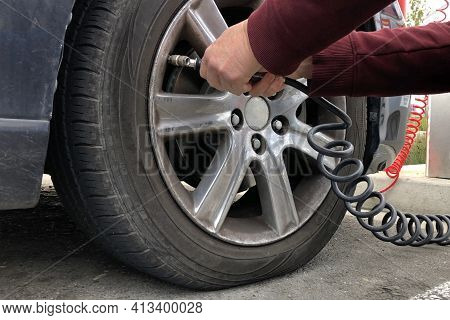 Close Up Of An Older Woman, Female Hands Using Automated Air Pump To Inflate Car Tire With Low Press