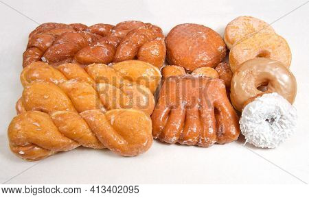 Variety Of Donuts Arranged On Parchment Paper Clustered Together. Bear Claw, Glazed Twists, Cinnamon