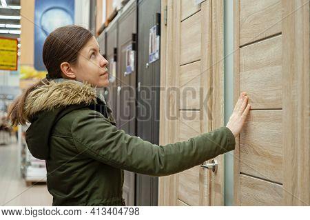 Buyer Chooses Door In Store. Shop Window Of Doors. A Large Selection Of Doors For House