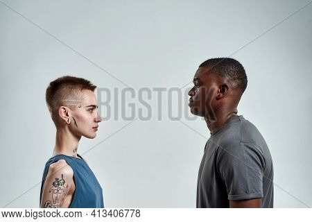 Young African American Man And Caucasian Woman Looking At Each Other While Standing Sideways To Came