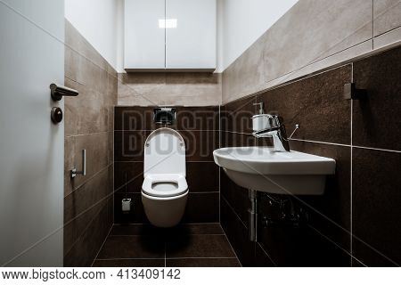 Small Modern Restroom With All Furnishings, Including A Small Sink And  Cabinet Mounted On The Wall.