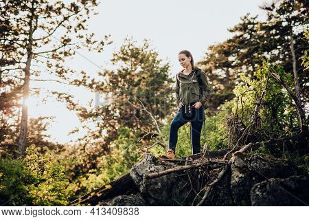 Beautiful Young Girl, In Outdoor Clothing With Camelbag, Standing On Raised Rock In Middle Of Wilder