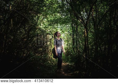 Young Woman Standing In Middle Of Dense Vegetation Forming Narrow Alley. Soft Light Shines Through V