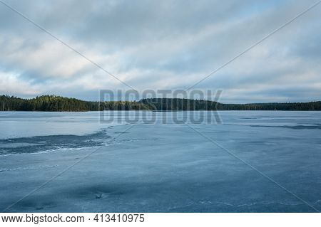 Frozen Lake In Wilderness With Forest On Horizon And Sky With Floating Clouds. Ice Has Soft Melting