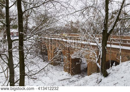 Ruins Of  Old Abandoned Koretsky Castle In The Snow. Arched Stone Bridge Leading To The Castle. Kore