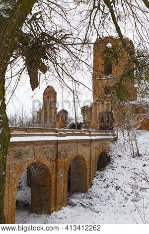 Ruins Of  Old Abandoned Korets Castle  In The Snow. Arched Stone Bridge Leading To The Castle. Koret