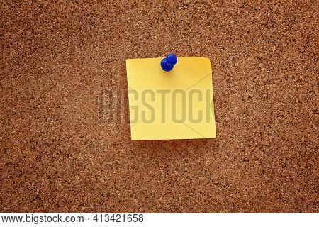 A Blank Paper Note Pinned On A Cork Board. Close Up.