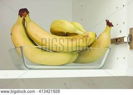 Bunch Of Bananas In A Glass Container That Is In A Kitchen Cupboard. Close Up.