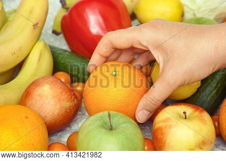A Person Taking An Orange Out Of A Pile Of Fruit And Vegetables. Close Up.