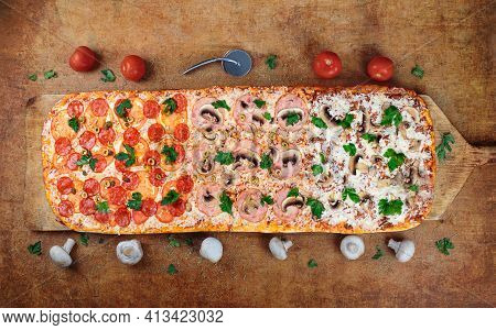 Long Pizza Mix Lies On A Wooden Table. Roman Pizza On A Wooden Spatula. The Pizza Is One Meter Long.