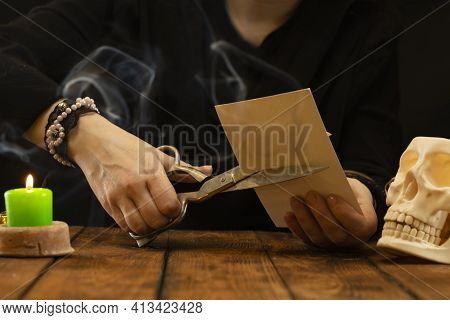 A Fortune-teller Or Oracle Cuts A Photograph With Large Scissors. Divination For Separation From A L